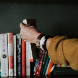 Women picking a book off of a shelf.