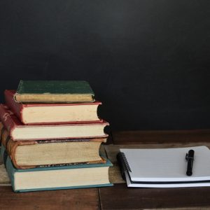 Stack of books next to a journal.
